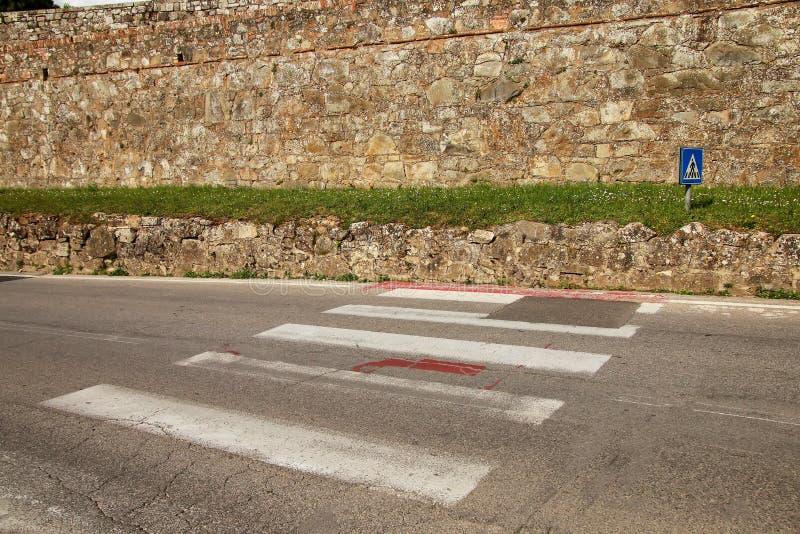 O cruzamento pedestre marcado esse termina na parede da cidade em Montalc foto de stock
