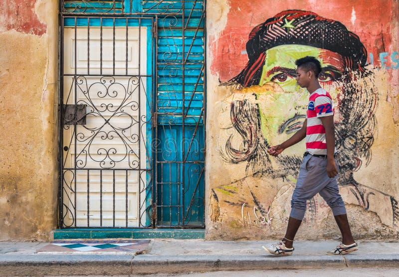 O cubano novo anda por um retrato de Che Guevara em Havana velho fotografia de stock
