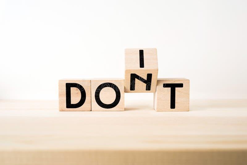 O cubo de madeira geométrico abstrato surreal com ` T da palavra DON e FAZ o conceito da TI no assoalho de madeira e no fundo bra imagem de stock royalty free