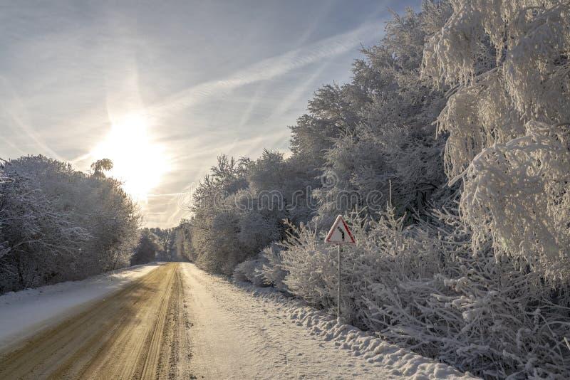 O cuidado do sinal de estrada gerencie sobre a estrada do inverno fotografia de stock royalty free