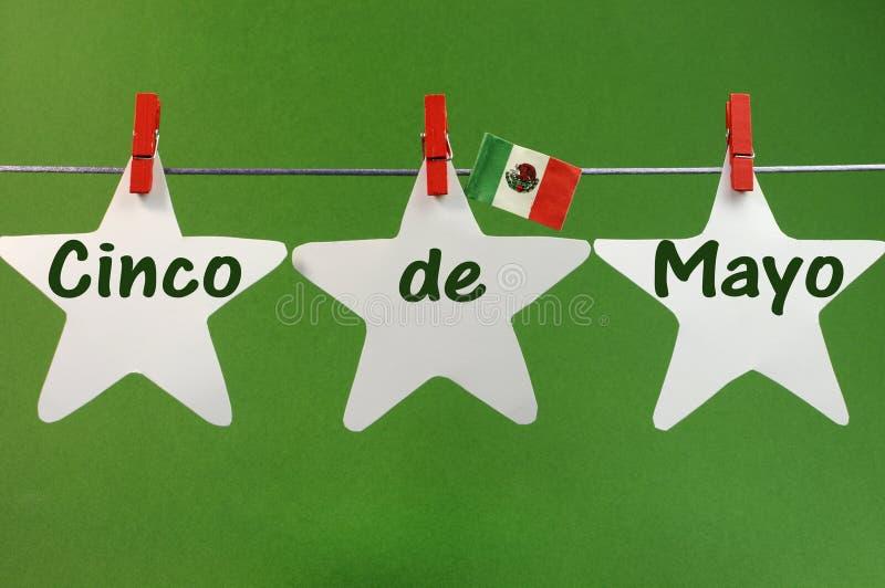 O cumprimento da mensagem de Cinco de Mayo escrito através das estrelas brancas e México embandeiram Pegs de suspensão em uma linh fotos de stock
