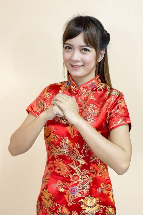 O cumprimento da mulher no chinês tradicional ou no cheongsam com expressão da boa vinda do elevador da mão e afortunados asiátic fotos de stock