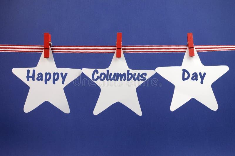 O cumprimento feliz da mensagem de Columbus Day escrito através da estrela branca carda a suspensão da fita e dos Pegs das listras fotografia de stock