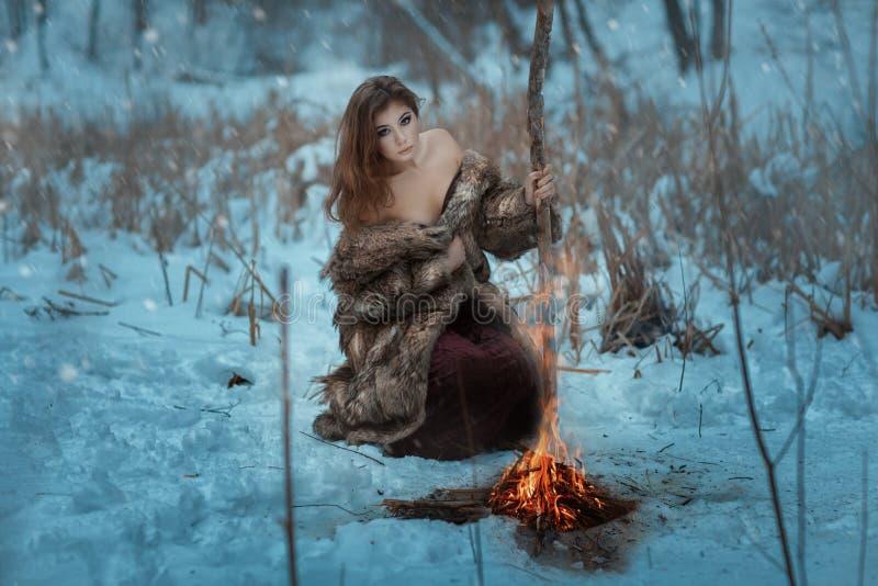 O curandeiro da menina é caloroso pelo fogo na floresta do inverno fotografia de stock