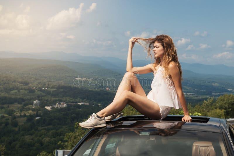 O curso bonito da mulher pelo carro e aprecia a opinião da natureza da viagem por estrada que senta-se no telhado no dia de verão fotos de stock royalty free