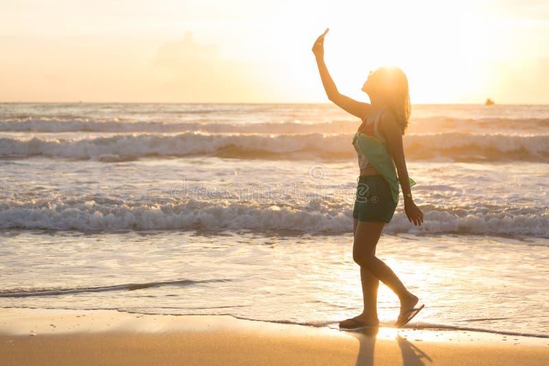 O curso da mulher aprecia toma um selfie da foto na praia com nascer do sol foto de stock
