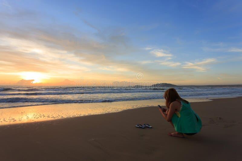 O curso da mulher aprecia toma uma foto na praia com nascer do sol foto de stock royalty free