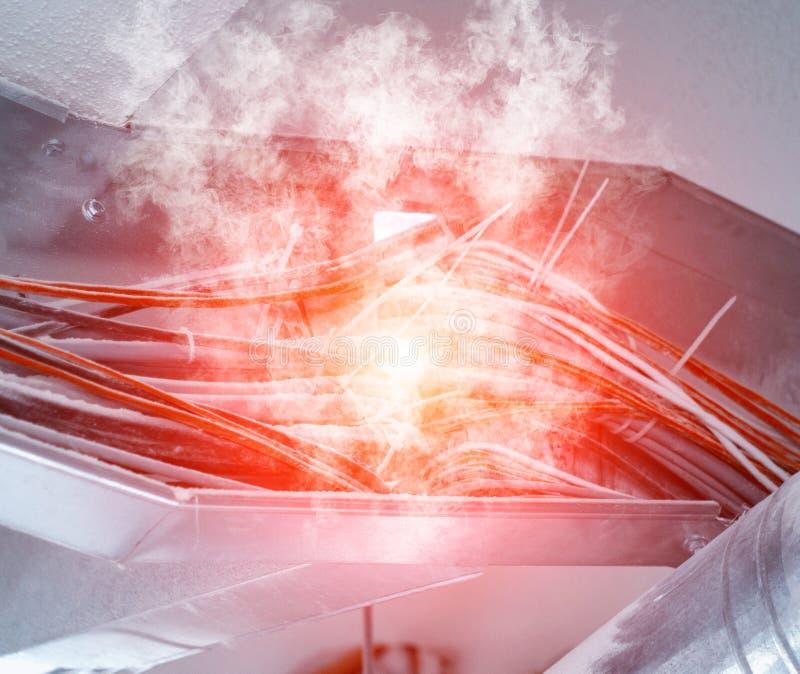 O curto-circuito da fiação, a fiação de fios bondes derrete e fuma, fogo e fumo, close up, cabo fotos de stock