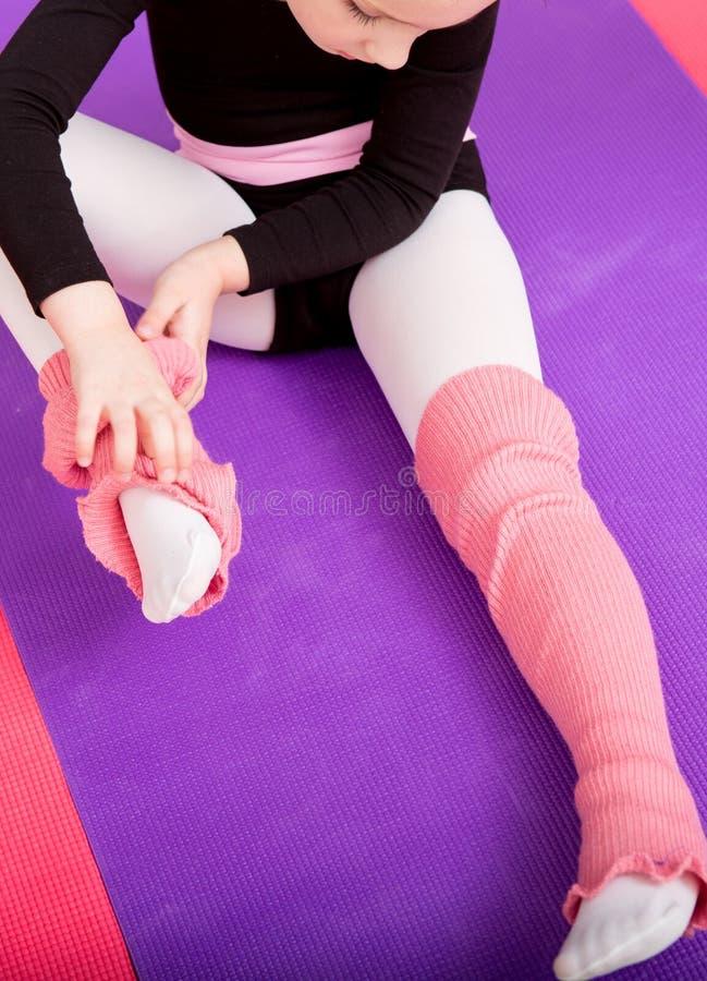 O dançarino da bailarina da menina corrige esteiras da roupa fotografia de stock royalty free
