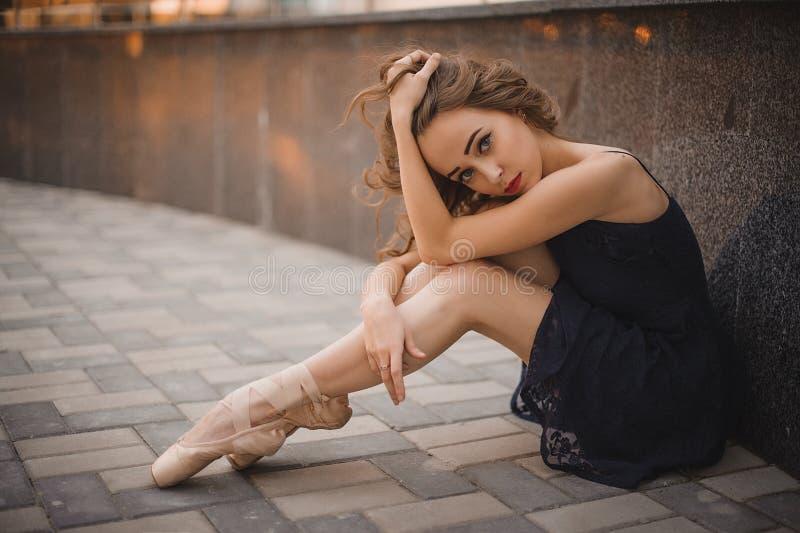 O dançarino de bailado no vestido e no pointe pretos calça o assento na terra imagens de stock royalty free