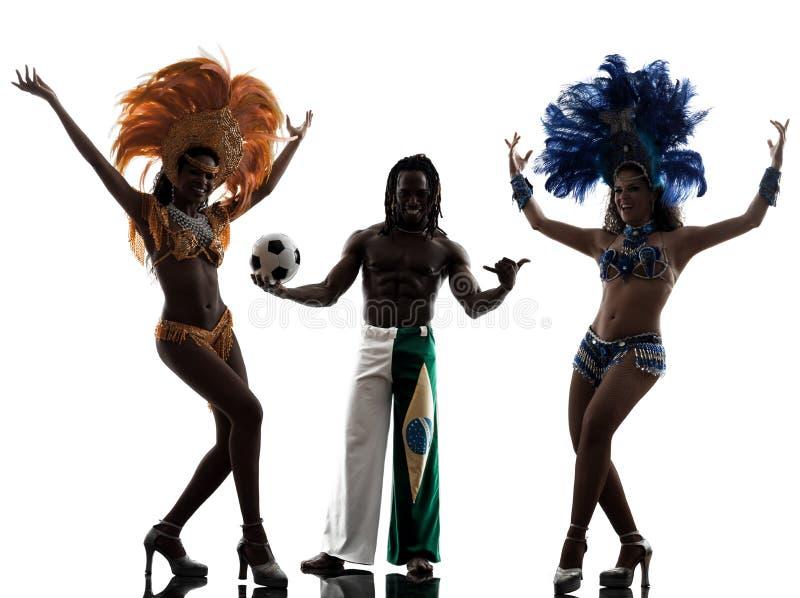 O dançarino do samba das mulheres e o jogador de futebol equipam a silhueta foto de stock royalty free
