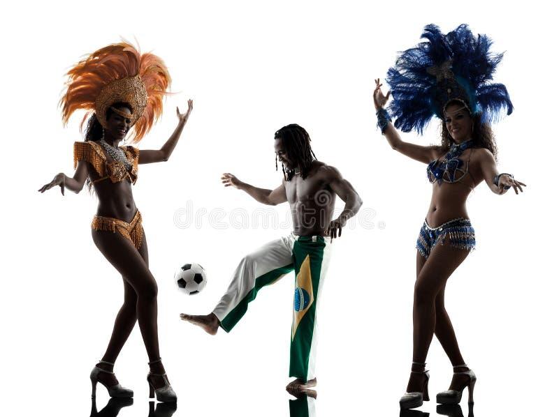 O dançarino do samba das mulheres e o jogador de futebol equipam a silhueta fotos de stock royalty free
