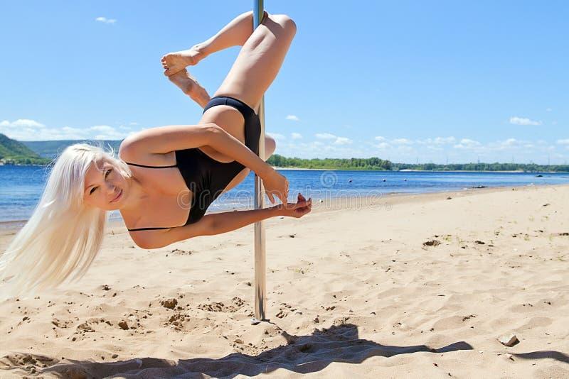 O dançarino louro executa acrobático no polo imagens de stock