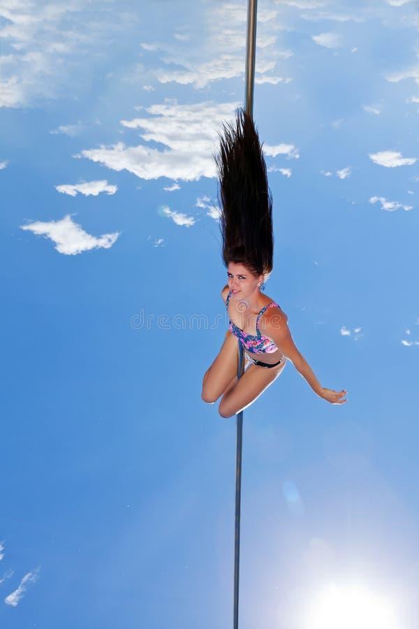 O dançarino no polo executa acrobático foto de stock royalty free