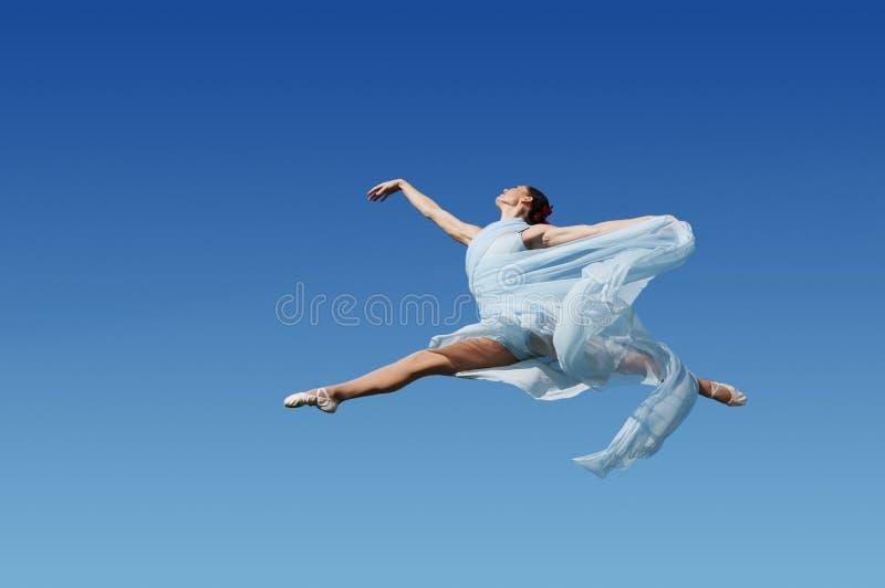 O dançarino que salta de encontro à SK azul foto de stock royalty free