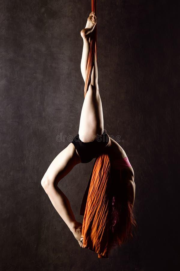 O dançarino 'sexy' bonito na seda aérea, contração graciosa, acrobata executa um truque no fitas fotografia de stock royalty free