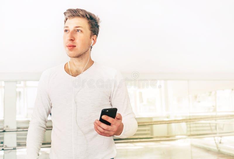 O dan?arino da arte moderna vestiu na roupa branca a escuta uma m?sica com a utiliza??o do smartphone fones de ouvido no sal?o do fotografia de stock royalty free