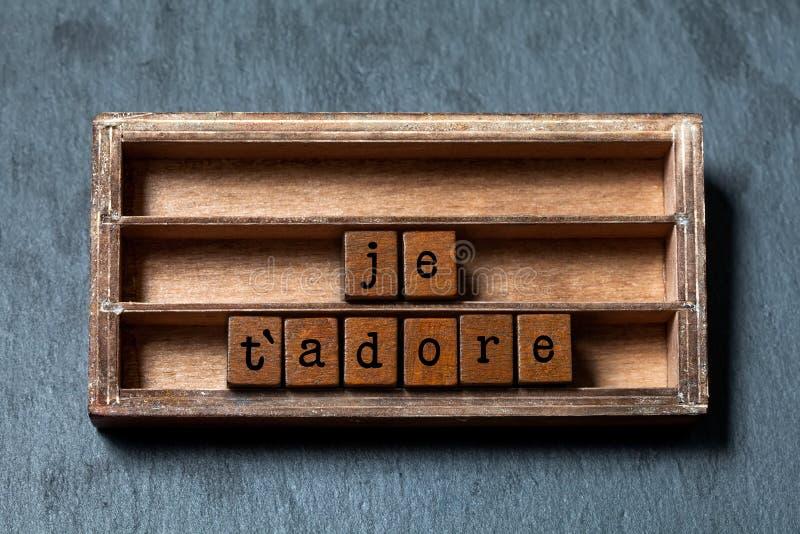 O ` de Je t adora Eu amo adorar-lo na tradução francesa A caixa do vintage, cubos de madeira fraseia escrito com letras do estilo imagem de stock