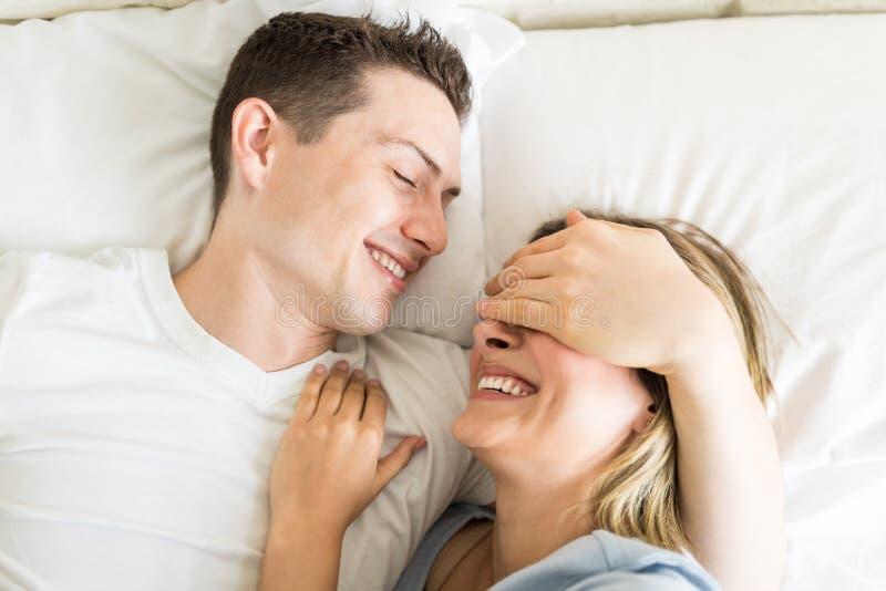 O ` de sorriso masculino brincalhão s da mulher da coberta Eyes na cama imagem de stock
