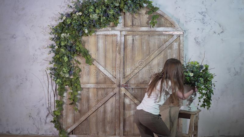O decorador bonito da menina leva um vaso das flores e põe sobre uma escadaria pequena do vintage contra um photozone bonito imagens de stock