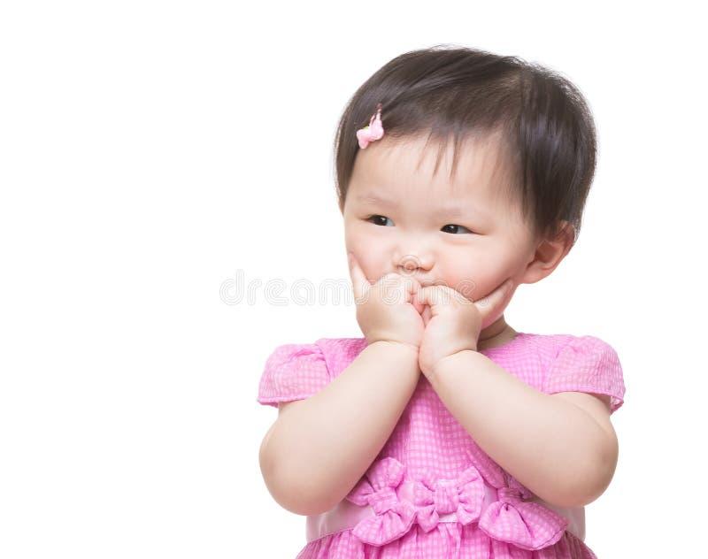 O dedo asiático da menina toca em sua cara fotografia de stock royalty free