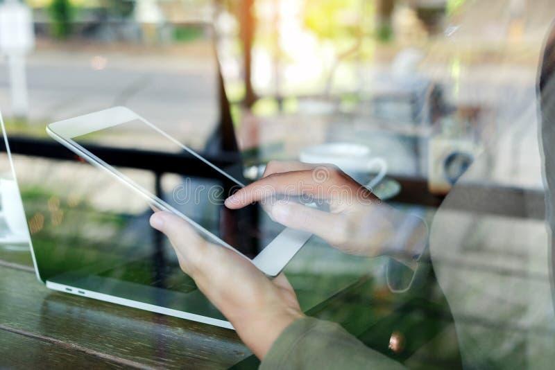 O dedo da mulher que toca na tabuleta digital vê completamente o vidro no cof foto de stock