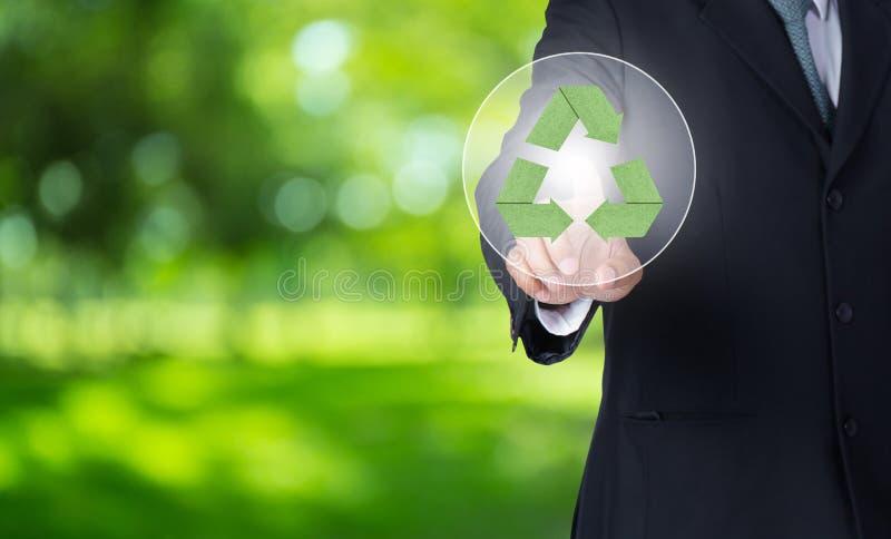 o dedo do homem de negócio que aponta no verde de papel recicla o símbolo com fundo da natureza imagens de stock royalty free