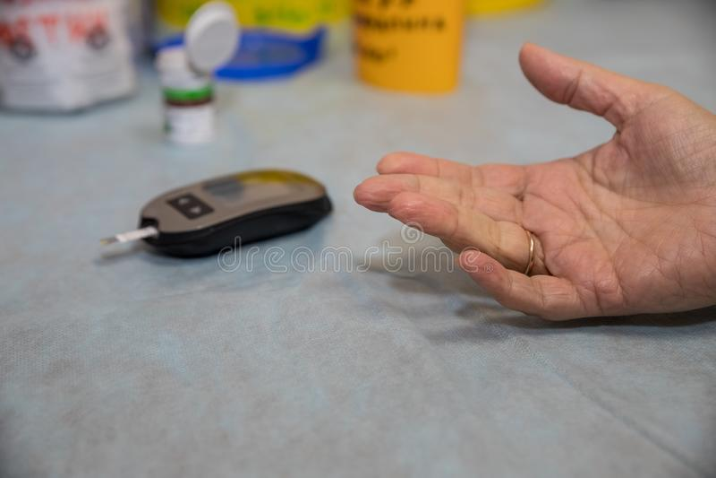 O dedo do paciente fêmea superior do doutor Using Glucometer On A mulher superior do diabético está tendo uma verificação acima n imagens de stock royalty free