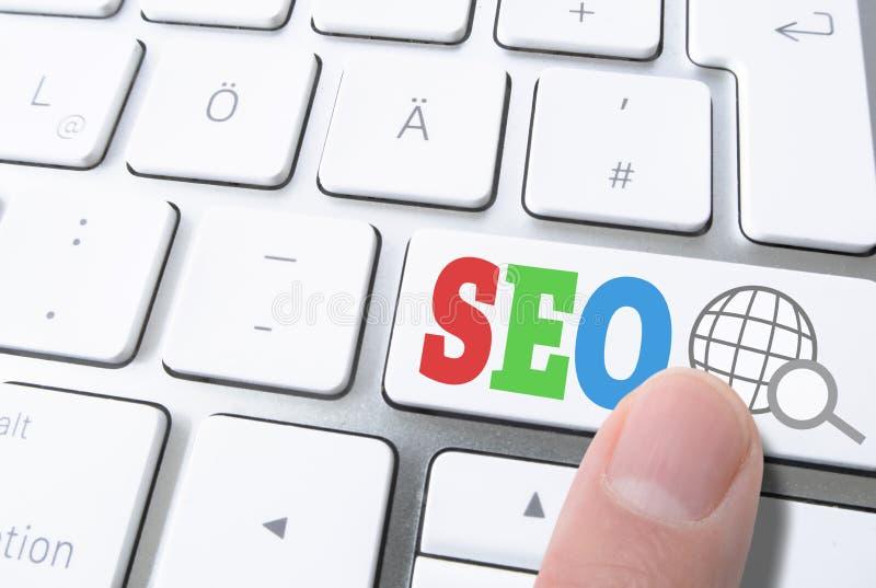 O dedo que pressiona a chave etiquetou SEO, otimização do Search Engine, no teclado de computador imagens de stock