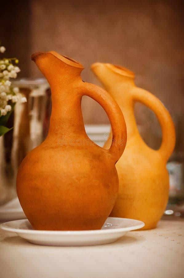 O delicado focalizou os jarros do vinho de cor da terracota na tabela, simples imagem de stock royalty free