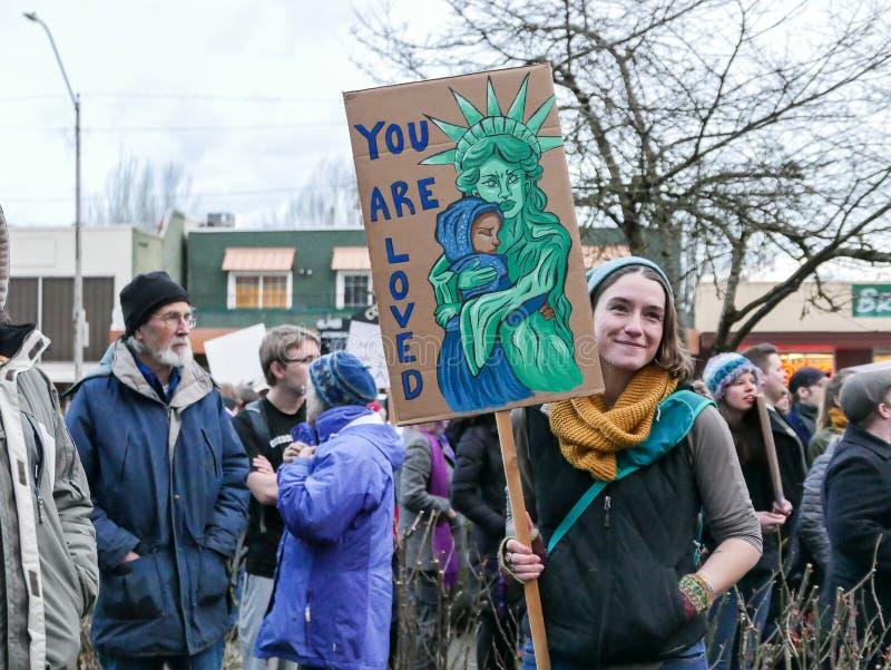 O demonstrador do Anti-trunfo guarda o sinal emocional da estátua da liberdade na reunião de Oregon imagem de stock