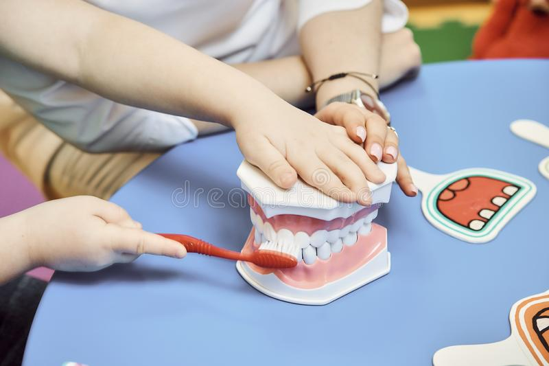 O dentista da mulher ensina a menina escovar seus dentes fotografia de stock royalty free