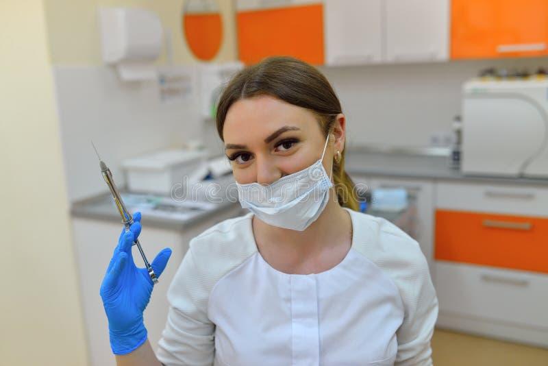O dentista do cirurgião na máscara que guarda a seringa para injetar fotos de stock royalty free