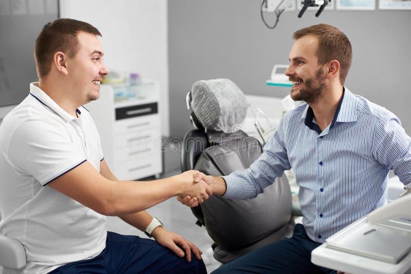 O dentista e seu cliente masculino atrativo estão agitando as mãos e estão sorrindo em um escritório dental fotos de stock