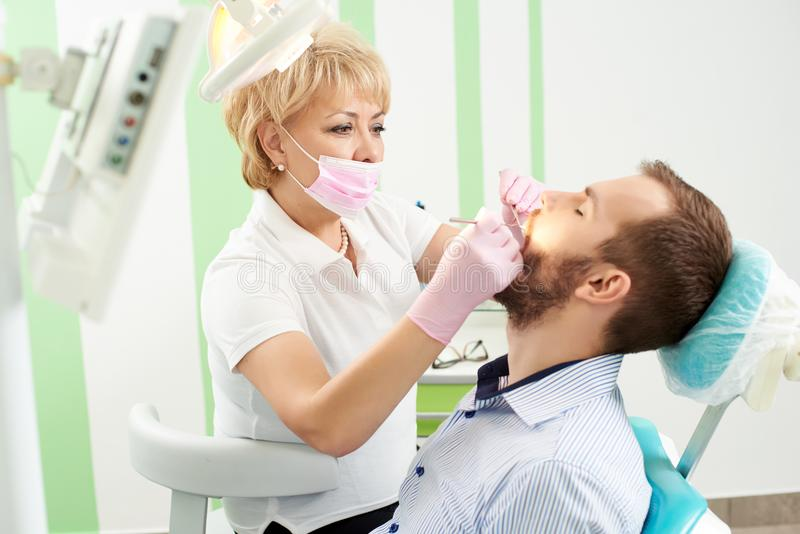 O dentista fêmea bonito que veste a máscara cor-de-rosa está atendendo aos dentes de um cliente masculino novo da odontologia mod fotografia de stock royalty free