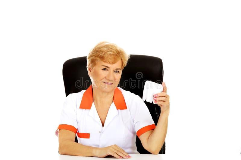 O dentista fêmea idoso do sorriso que sentam-se atrás da mesa e o dente grande das posses modelam foto de stock royalty free