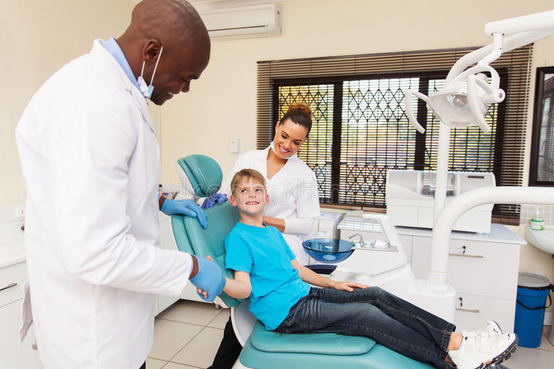 O dentista felicita o rapaz pequeno fotos de stock royalty free