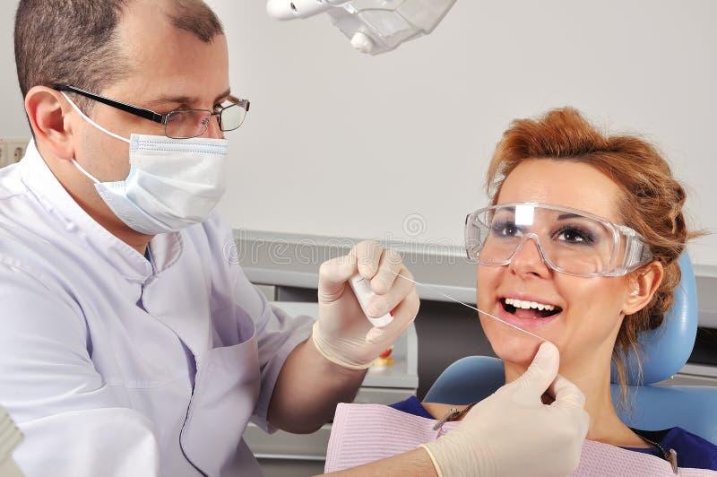 O dentista limpa os dentes imagem de stock