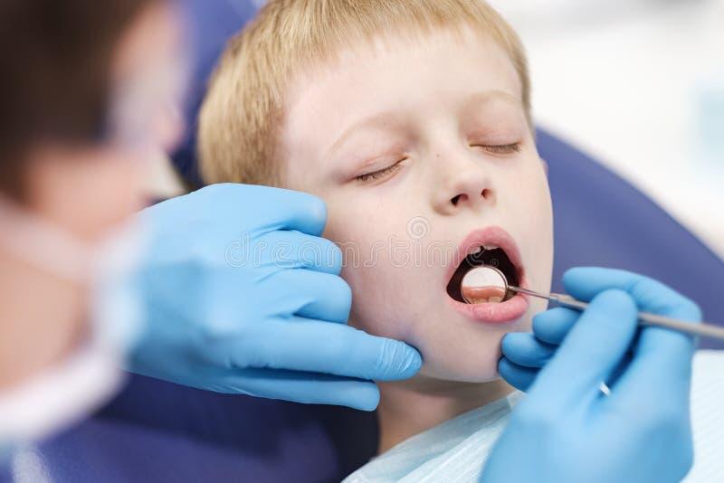 O dentista masculino examina os dentes do menino alegre paciente fotos de stock