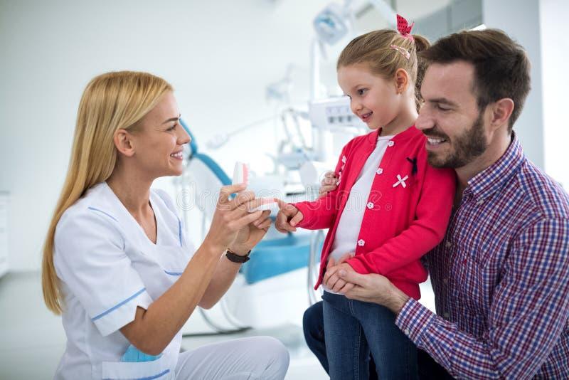 O dentista mostra a menina e a sua maxila do ` s do paizinho com dentes foto de stock royalty free