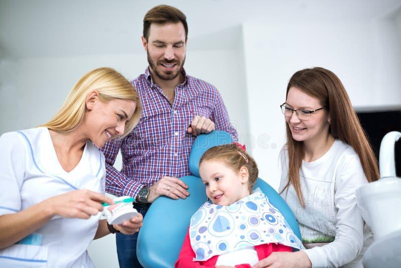 O dentista mostra a uma menina como lavar seus dentes fotos de stock royalty free