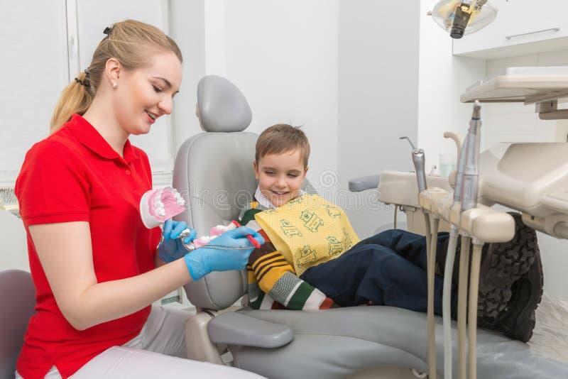 O dentista que mostra ao rapaz pequeno como limpar os dentes com uma escova de dentes em um manequim artificial da maxila imagens de stock royalty free
