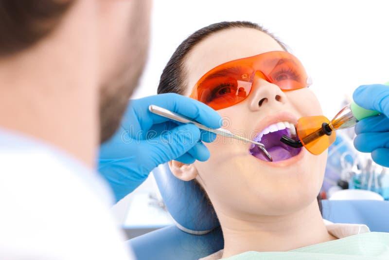 O dentista usa a lâmpada do photopolymer para curar os dentes fotos de stock royalty free