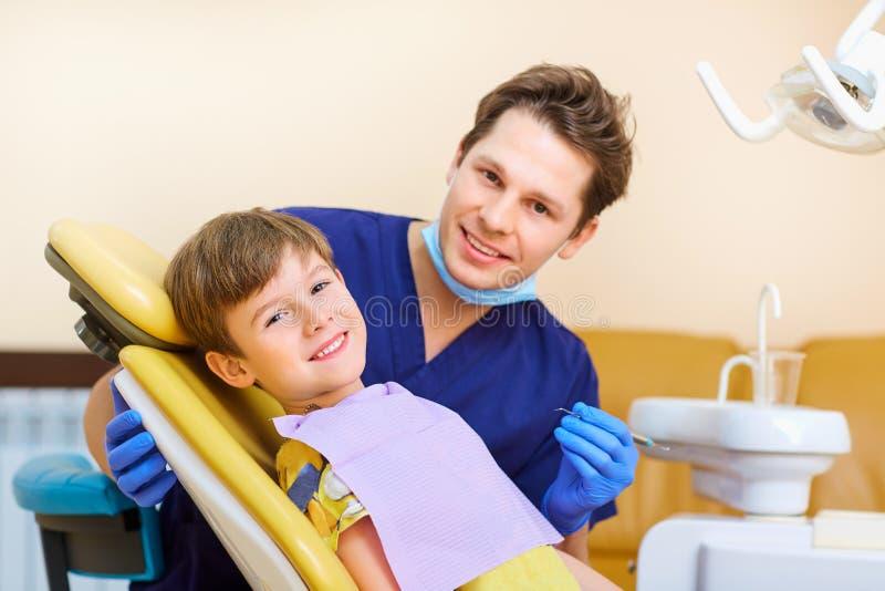 O dentista verifica os dentes de um adolescente do menino do homem fotografia de stock