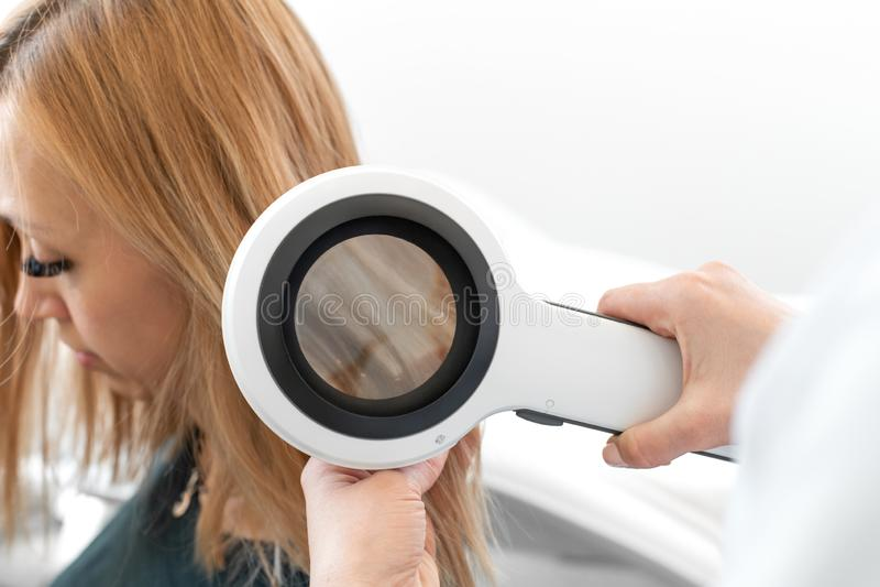 O dermatologista do trichologist do médico examina o estado do cabelo do paciente e das raizes do cabelo com um dermatoscope imagem de stock