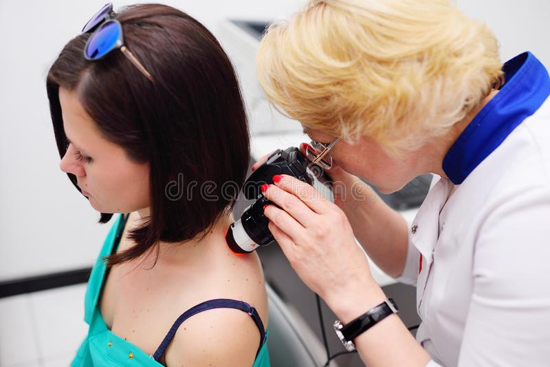 O dermatologista examina as toupeiras ou a acne do paciente com um dermatoscope imagem de stock royalty free
