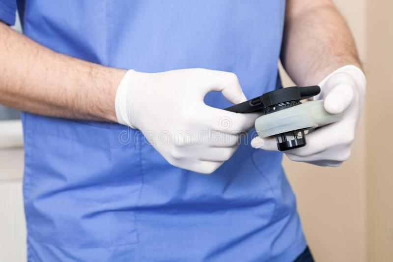 O dermatologista examina a toupeira do dispositivo do câncer do teste o controle da mão que que verifica a varredura checkout o t foto de stock royalty free