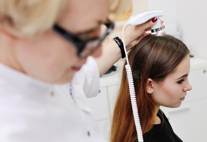 O dermatologista examina um cabelo paciente da mulher usando um dispositivo especial imagem de stock