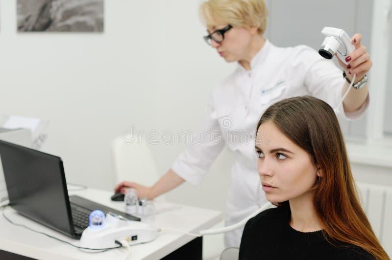O dermatologista examina um cabelo paciente da mulher usando um dispositivo especial fotografia de stock