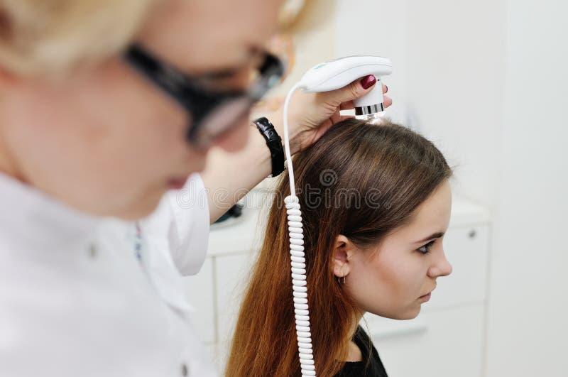 O dermatologista examina um cabelo paciente da mulher usando um dispositivo especial foto de stock
